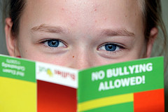 child reading book titled No Bullying Allowed