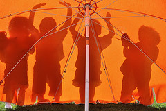 shadows of children playing as seen through summer umbrella