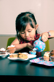 little girl pouring out tea with cookies