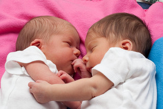 two newborn babies sleeping together