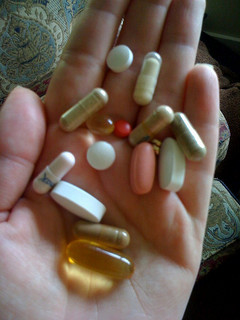 hand holding several vitamin pills