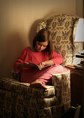 young girl sitting in chair reading a book