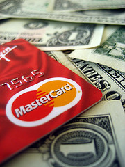 corner of mastercard laying on top of dollar bills