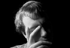 man leaning face on hand