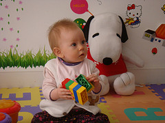 baby in playroom holding toy