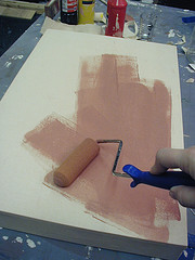 person rolling gesso onto blank painter canvas