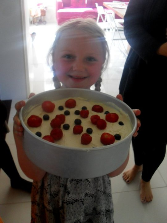 girl holding cheesecake with berries on top
