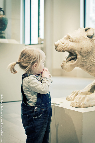 girl in museum looking at lion sculpture