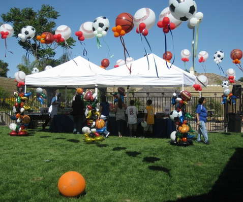 party tent with sports themed balloons flying overhead