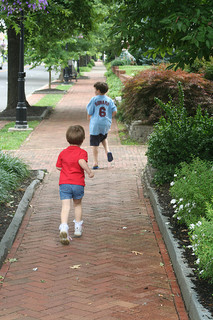two children running down sidewalk