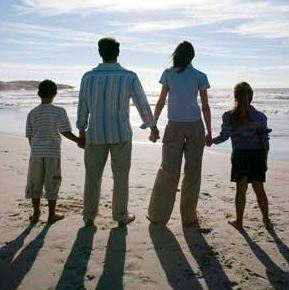 two parents and two children standing on beach, facing the water