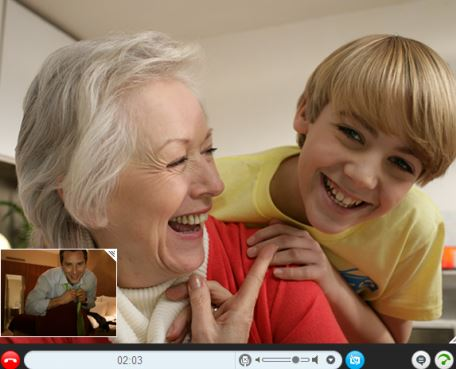 boy leaning over grandma's shoulder, both are laughing