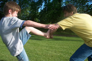 dad teaching son how to block a kick