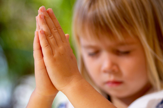 young girl with folded hands praying