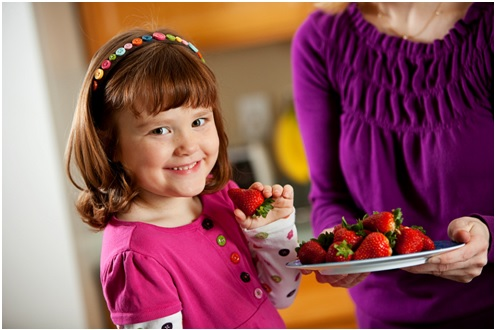 girl smiling ready to eat a strawberry