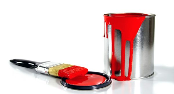 red paint spilling over side of paint can, brush resting on lid
