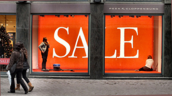 Women walking past sale sign in window