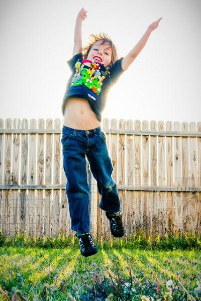 Boy jumping in backyard
