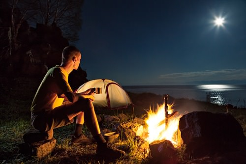 young man sitting at a campfire on ridge overlooking water