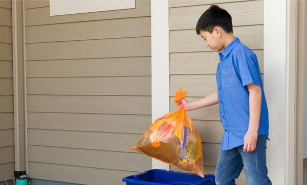 boy placing orange Hefty EnergyBag filled with plastics into recycling bin
