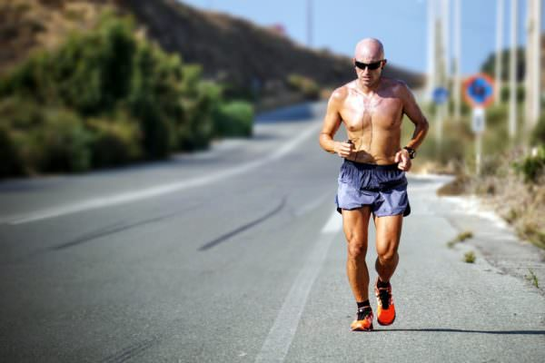 shirtless man, running by roadside