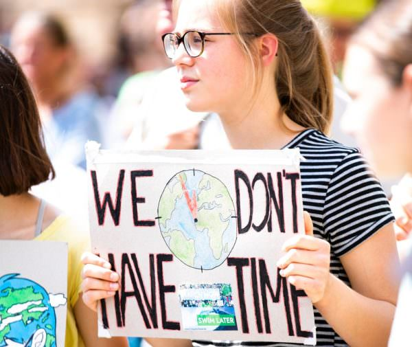 young woman holding sign at climate change protest