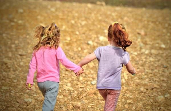 two young girls holding hands and walking in open space