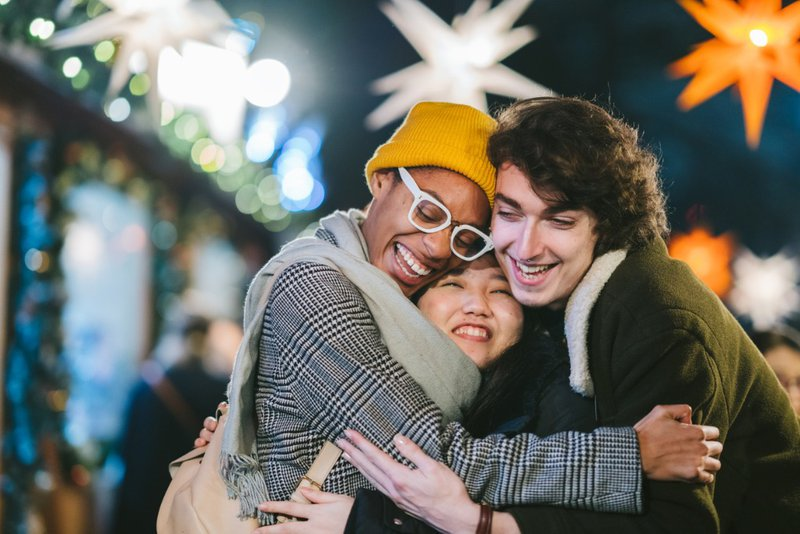 three loving friends hugging