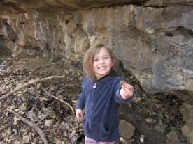 Pretty Rynae finding treasures at the base of this natural rock wall
