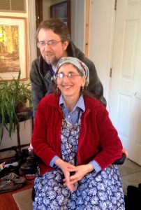 Maxine, Don helping and supporting behind her wheelchair.