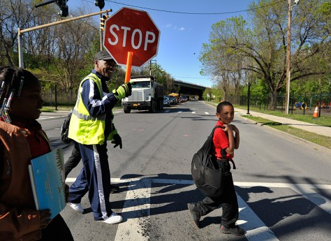 School crossing guard and Ezra Prentice Homes resident, Be Be White, stops traffic on South Pearl Street for children, including his son Brayton and Sanaiya , both six years old, to cross over to the apartments on May 9, 2016.