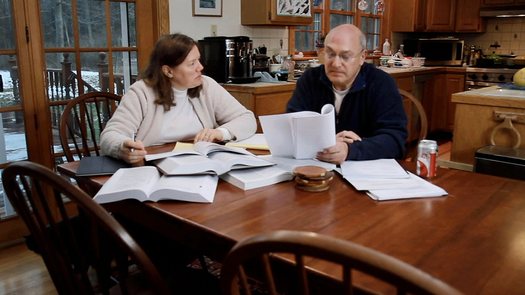 Helen and David Slottje go over paperwork at their kitchen table.