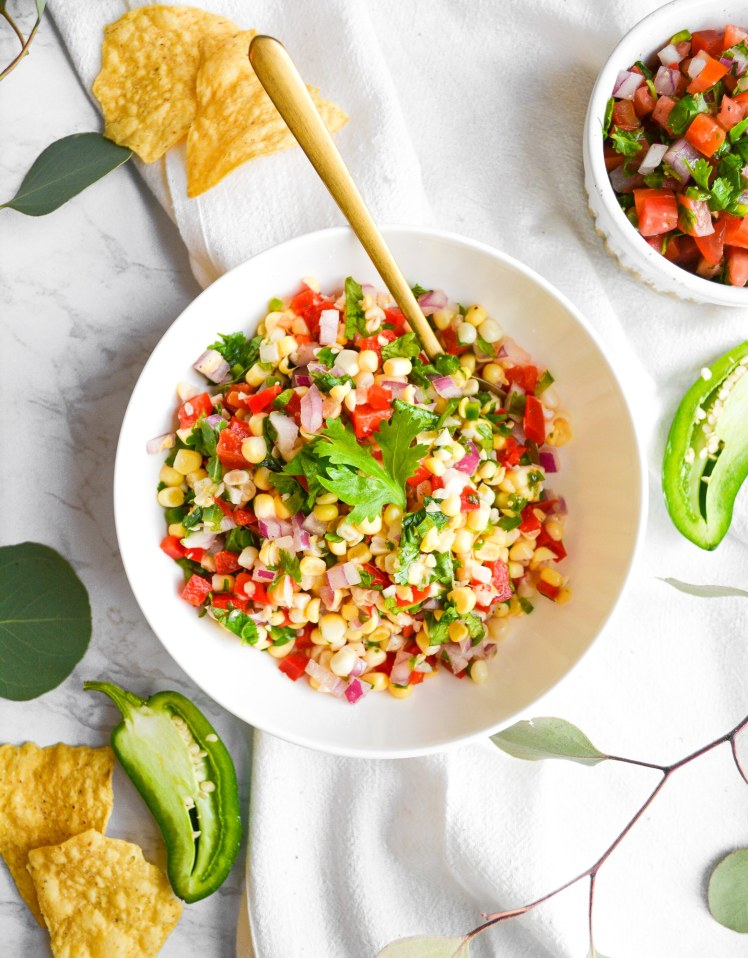 Overhead shot of Easy Corn Salsa in a white bowl with a gold spoon