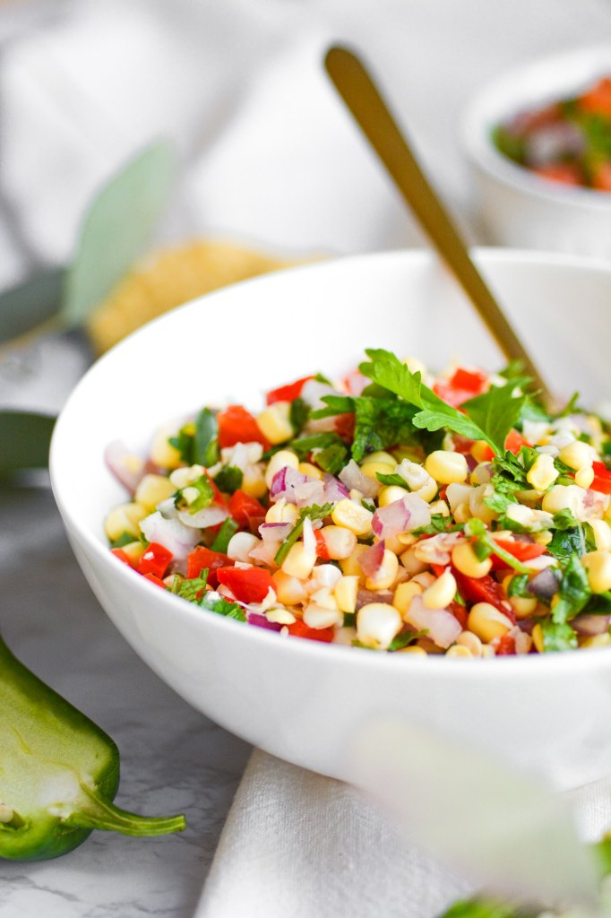 Close up of salsa in a white bowl with a gold spoon