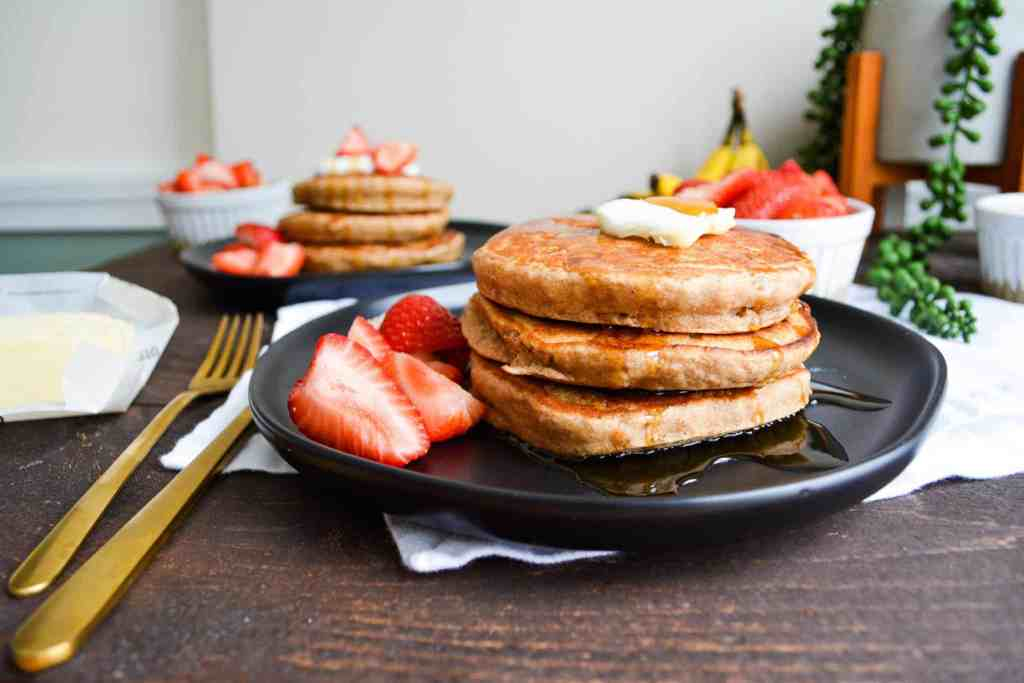 close up of stacked pancakes with butter and syrup