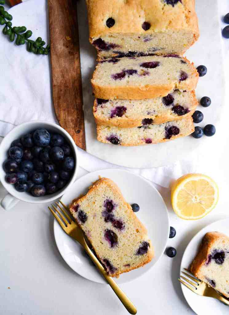 Slice of One-Bowl Blueberry Lemon Loaf on a plate with a cup of blueberries