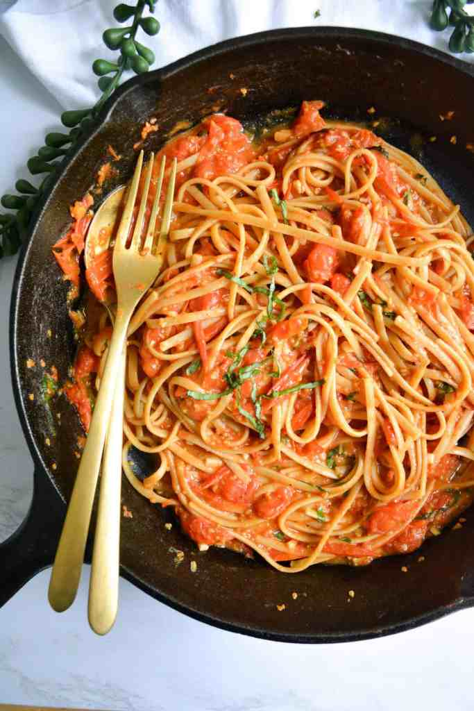 Close up on Fresh Cherry Tomato + Basil Pasta in a cast iron pan