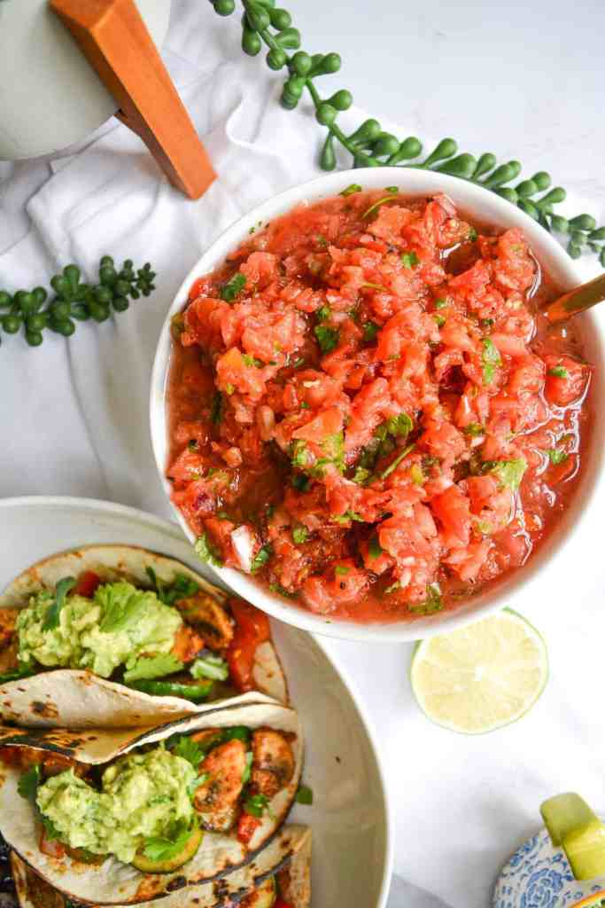A bowls of Thick Restaurant Style salsa with tacos
