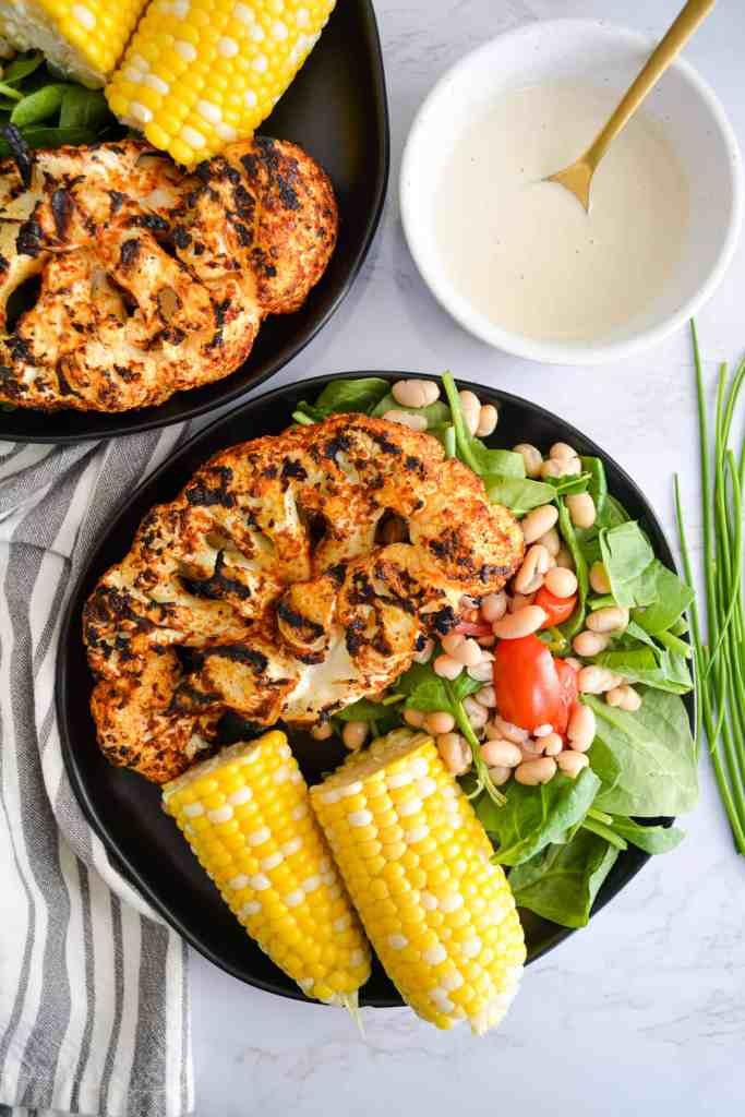 Portrait of two plates with grilled cauliflower corn and salad