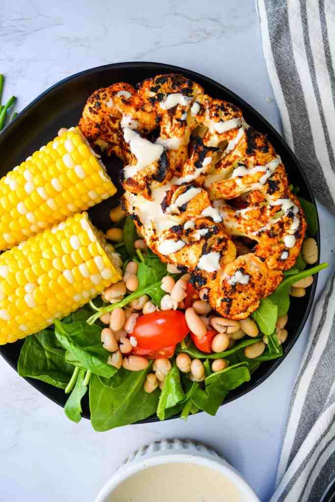 Portrait of Harissa Butter Grilled Cauliflower Steak with corn and salad