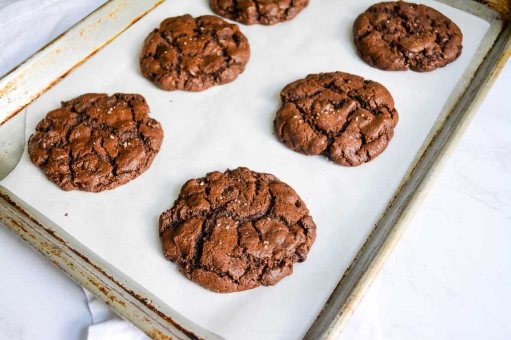 Freshly baked eggless double chocolate chip cookies on a sheet pan.