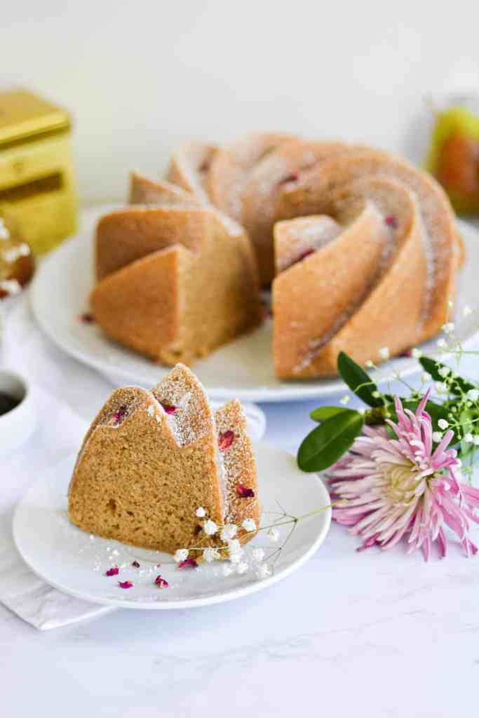 A slice of Bundt cake on a white plate next to puruple flowers