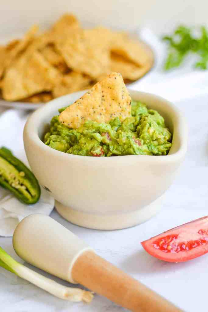 Easy and Chunky guacamole in a mortar with a tortilla chip in it