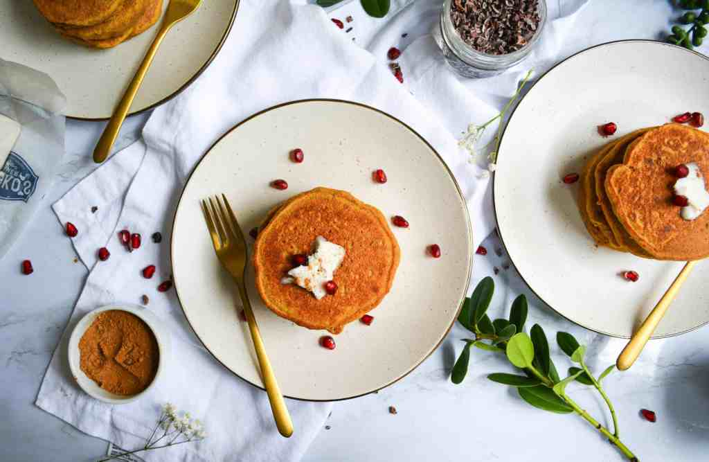 3 tan plates with Whole Grain Pumpkin Spice Pancakes topped with pomegranate arils