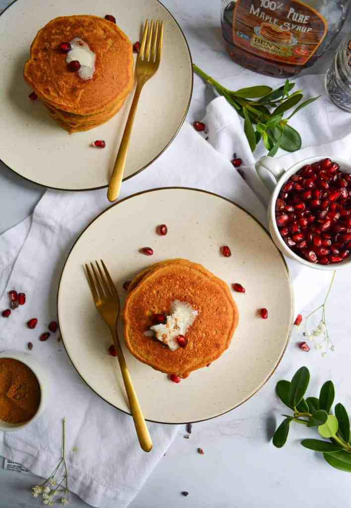 2 plates of whole grain pumpkin spice pancakes topped with vegan butter and pomegranate arils