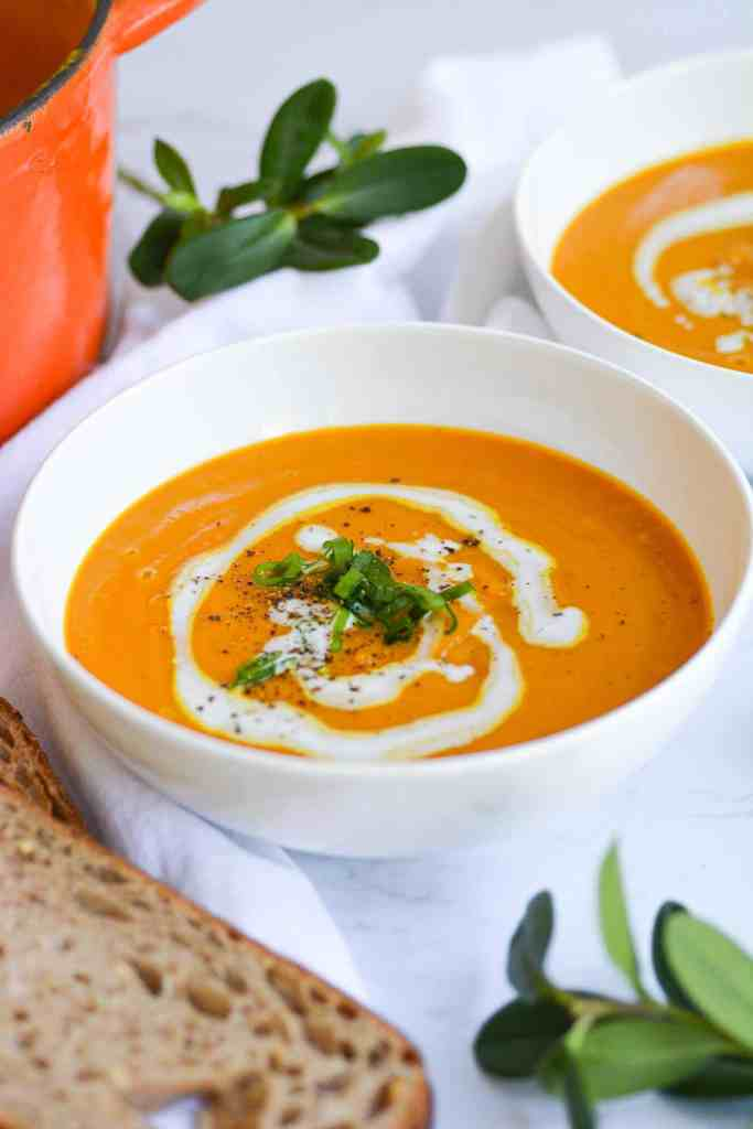 A bowl of Winter Squash Soup, decorated with a drizzle of coconut cream and green onions