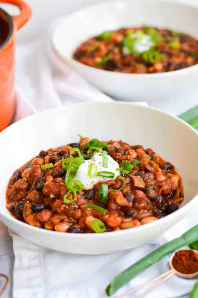 Two bowls of chili in white bowls topped with sour cream and scallions
