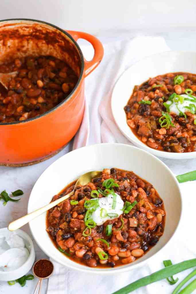 Two bowls of chili topped with sour cream and scallions next to an orange dutch oven