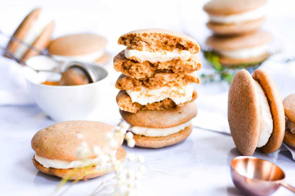 Landscape up stacked Chai Spiced whoopie pies with the top one cut in half on a white background by Earthly Bakers Co.