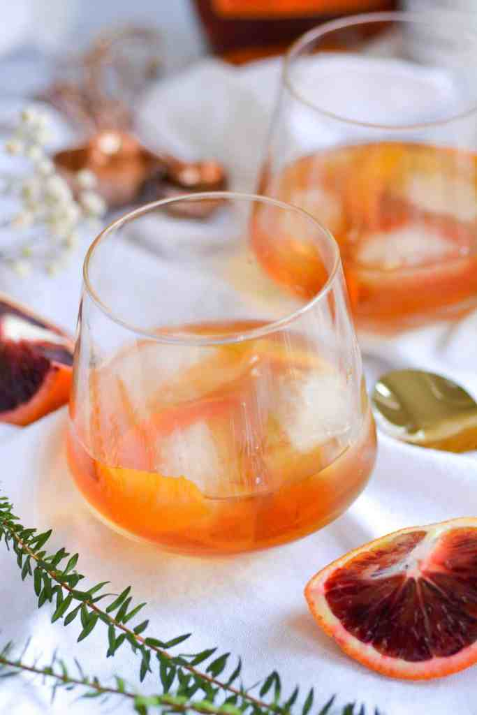 2 glasses of maple bourbon old fashioned on a white background with blood orange slices